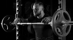 The weightlifter is near the bar. Put his hands on it for a respite Stock Photos