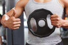 Weightlifter que sostiene el disco con los pulgares para arriba Fotos de archivo libres de regalías