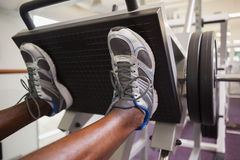 Weightlifter som gör benpressar i idrottshall arkivfoto