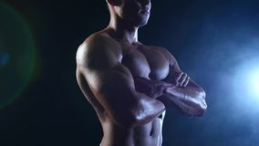 Weightlifter toont zijn lichaam, sterkte en duurzaamheid aan Zwarte rookachtergrond Langzame Motie stock video