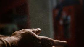 Weightlifter wrijft handen met magnesia, slaat zijn handen Wolk van magnesia stock footage