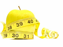 Weightloss. Isolated yellow apple surrounded by measuring tape Royalty Free Stock Photo