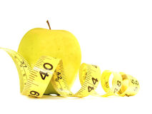 Weightloss. Isolated yellow apple surrounded by measuring tape Stock Images