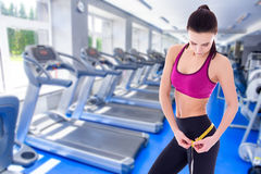 Weightloss concept - beautiful slim sporty woman with measure ta. Pe in modern gym Royalty Free Stock Photography