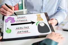 Weightloss concept on a clipboard. Businessman showing weightloss concept on a clipboard Stock Image