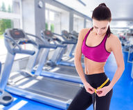 Weightloss and diet concept - beautiful slim sporty woman with m. Easure tape in modern gym Stock Photo