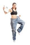 Weightloss kvinna som rymmer en viktscale royaltyfri fotografi