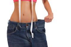 Weightloss - mujer que muestra la pérdida de peso en blanco Imágenes de archivo libres de regalías