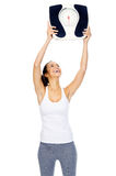 Weightloss scale woman. Woman with scale celebrating weightloss and a healthy fit body Royalty Free Stock Image