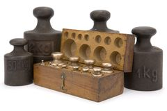 Weights. Vintage box with brass weights unit arranged in two row and surrounding iron weights unit on white background Royalty Free Stock Images