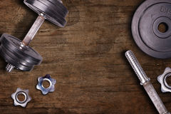 Weights at the gym whit handle and barbell. Stel gym equipment on dark wood floor background Stock Photo