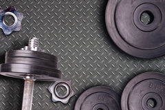 Weights at the gym whit handle and barbell. Stel gym equipment on metal floor background. Royalty Free Stock Photo