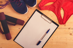 Weights, sneakers, sports bra, clipboard with pen Stock Images