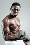 Weights training. Well built muscular black man pumping iron Stock Photography