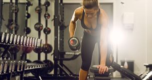 Focused fit woman training lats and lifting weights in fitness gym. Weights training woman in fitness gym lifting weights with a fit and strong body. Slow motion stock footage