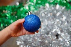 Weihnachten-Baumdekoration an Hand, glänzender Hintergrund stockbilder