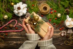 Weihnachten, der Hintergrund des neuen Jahres, Flachlage Mädchen in einer woolen Strickjacke wickelt Geschenke auf einem hölzerne lizenzfreies stockbild