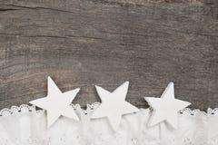 Weihnachten: drei weiße Sterne auf grauem hölzernem Hintergrund, Spitze sno Lizenzfreies Stockfoto