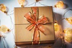 Weihnachten eine goldene Geschenkbox mit einem roten Bogen und eine schöne glühende Girlande gegen den Schnee lizenzfreies stockfoto