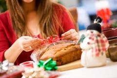 Weihnachten: Frau, die Geschenk des Bananenkuchens einwickelt Lizenzfreies Stockfoto