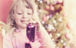 Weihnachten, glückliches kleines Mädchen mit Geschenk auf Weihnachtsabend lizenzfreies stockbild