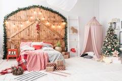 Weihnachten im Morgenschlafzimmer Doppelbett im Weihnachteninnenraum auf hölzernem Wandhintergrund stockfoto