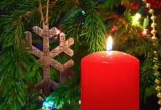 Weihnachten - Kerze und hölzerne Schneeflocke auf Tanne Stockfotografie