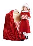 Weihnachten: Kleines Mädchen steht nahe bei Sack Feiertags-Geschenken Lizenzfreie Stockfotografie