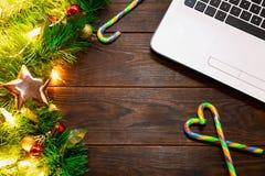 Weihnachten, Konzept des neuen Jahres - weißer Laptop, Zuckerstange, Tannenbaumaste und -bälle, goldener Stern und Girlande von g lizenzfreie stockfotografie