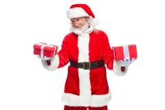 Weihnachten Lächelnde Santa Claus in den weißen Handschuhen hält zwei Kästen mit Geschenken Das Konzept des Wählens eines Geschen stockfotografie