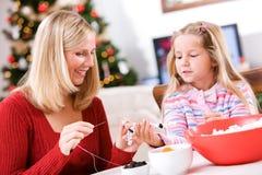 Weihnachten: Mädchen-helfende Mutter mit Spaß-Popcorn Garland Decorati Lizenzfreie Stockfotos