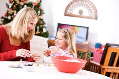 Weihnachten: Mädchen und Mutter arbeiten zusammen an Popcorn-Girlande Stockbilder