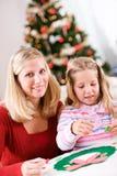 Weihnachten: Mädchen und Mutter, die an Feiertags-Handwerk arbeiten Lizenzfreie Stockfotos