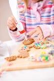 Weihnachten: Mädchen verziert Lebkuchen-Mann mit Zuckerglasur Stockfoto