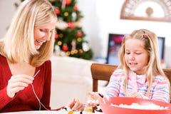 Weihnachten: Mutter und Kind machen Feiertag Garland From Popcorn An Stockbild