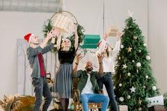 Weihnachten, neues Jahr, Winterurlaube Vier Freunde, die Weihnachten am gemütlichen Haus, Spaß mit Präsentkartons habend feiern stockfotos