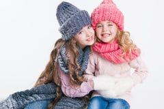 Weihnachten Neues Jahr Zwei kleine Schwestern halten anwesend in der Winterkleidung Rosa und graue Hüte und Schals familie Winter lizenzfreies stockbild