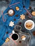 Weihnachten oder Zusammensetzung des neuen Jahres mit Lebkuchen, Zuckerstange und Kaffeetasse auf dunklem Hintergrund Flache Lage Stockbild