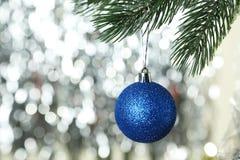 Weihnachten-pinecone auf Weihnachtsbaum auf Lichtern Hintergrund, Abschluss oben Lizenzfreie Stockfotos