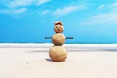 Weihnachten positives Sandy Snowman in rotem Santa Claus-Hut am Ozeansonnenuntergangstrand Lizenzfreie Stockfotografie