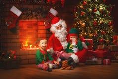 Weihnachten Santa Claus mit Elfen-Getränk-Milch und essen Plätzchen lizenzfreies stockfoto