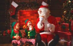 Weihnachten Santa Claus mit Elfen-Getränk-Milch und essen Plätzchen lizenzfreie stockbilder