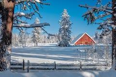 Weihnachten sceen von einer roten Scheune im Winterschnee stockbild