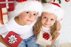 Weihnachten scherzt mit Sankt-Hüten und Geschenken Stockbild