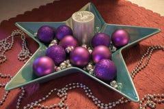Weihnachten, silberne Kerze mit purpurroten Weihnachtsbällen Stockfotografie