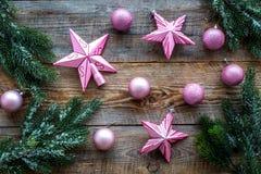 Weihnachten spielt nahe Kiefernniederlassungen auf Draufsicht des hölzernen Hintergrundes Lizenzfreie Stockbilder