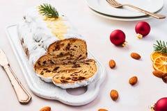 Weihnachten-Stollen-Kuchen mit Puderzucker, Marzipan, Mandeln und Rosinen auf weißer dienender Platte lizenzfreies stockbild