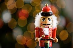 Weihnachten: Traditioneller hölzerner Nussknacker mit Baum hinten Lizenzfreies Stockbild