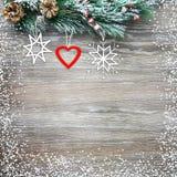 Weihnachten- und neues Jahr ` s Zusammensetzung Die Kiefernkegel, Fichtenzweige auf einem hölzernen Hintergrund Stockfotografie