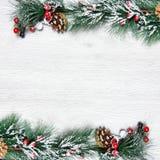 Weihnachten- und neues Jahr ` s Zusammensetzung Die Kiefernkegel, Fichtenzweige auf einem hölzernen weißen Hintergrund Stockfotografie